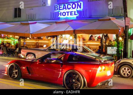 Miami Beach Florida Art Deco District Ocean Drive dusk evening night palm trees Beacon hotel buildings neon traffic - Stock Photo