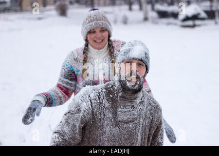 Cute young hipster couple covered in snow in the middle of a snowball fight - Stock Photo