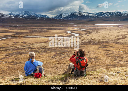 Hikers enjoy view of the Nigu river, Brooks range, Gates of the Arctic National Park, Alaska. - Stock Photo