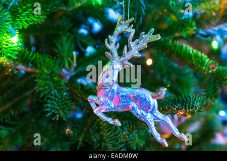 Christmas ornament in the form of a stag hanging in a Christmas tree. - Stock Photo