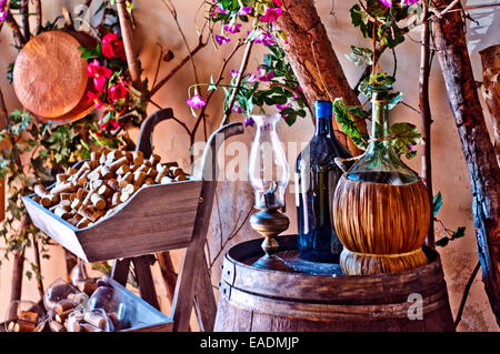 wine bottles, with bottle of olive oil, resting on an oak barrel cellar in a typical Italian - Stock Photo