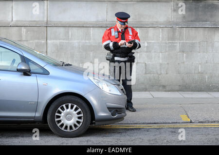 A traffic warden issues a parking ticket to an illegally parked car. - Stock Photo
