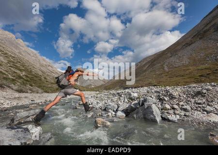 Creek,Hiker,Jumping,Alaska,Mountain - Stock Photo