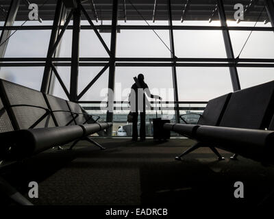 Silhouette of a person with a rolling suitcase in front of an airport terminal window - Stock Photo