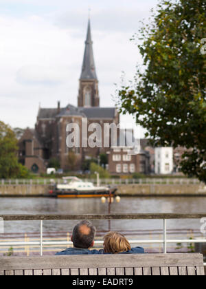 Middle aged couple embracing on a park bench in front of the river Maas and the St. Martinus church tower in Maastricht, - Stock Photo