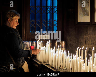 Woman lighting candle at the Basilica of Our Lady in Maastricht, The Netherlands - Stock Photo