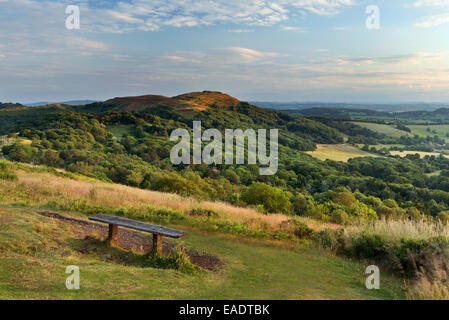 An old wooden bench on Black Hill, part of the Malvern Hills, has a stunning view across the Herefordshire - Stock Photo