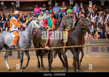Jockeys waiting for the start of Palio di Siena horse race on Piazza del Campo, Siena, Tuscany, Italy - Stock Photo