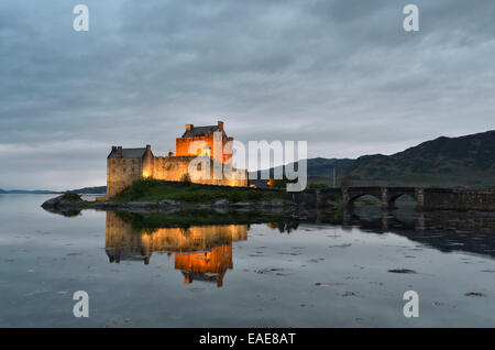Eilean Donan Castle, ancestral seat of the Scottish clan of Macrae, reflected in Loch Duich in the evening, Dornie, - Stock Photo