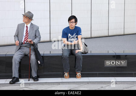 An older and a younger man sitting in front of the Sony Building in Ginza district in Tokyo, September 30, 2014. - Stock Photo
