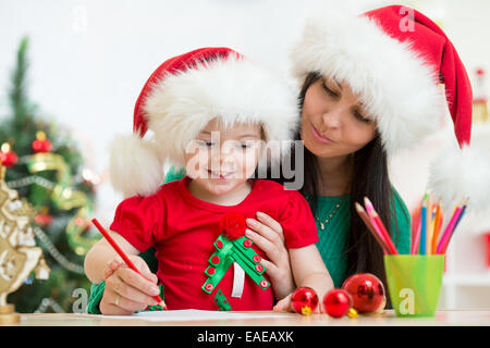 kid girl and mother writing letter to Santa - Stock Photo