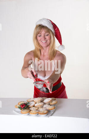 Woman in Santa outfit puts icing sugar topping onto Mince Pies a traditional Christmastime treat - Stock Photo