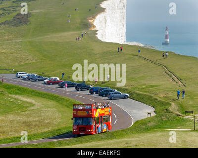 The White Cliffs and Beachy Head lighthouse with a Eastbourne City Sightseeing open top double decker tour bus - Stock Photo