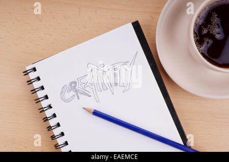 writing pad with the word creativity drawn in pencil and cup of coffee on desk - Stock Photo