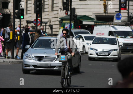 A cyclist traveling in front of traffic in London's Trafalgar Square - Stock Photo