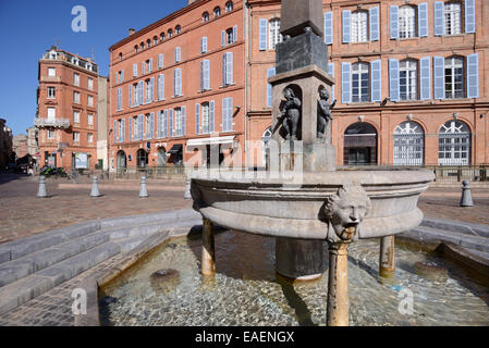 Street Fountain and Red Brick Architecture on Place Etienne or Town Square Toulouse Haute-Garonne France - Stock Photo