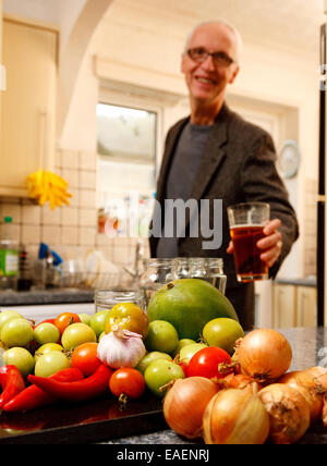 A man in a kitchen enjoying a pint of beer - the focus is on the ingredients that he will be using to make a chutney - Stock Photo