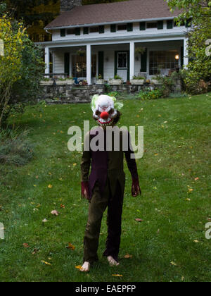 boy in Halloween costume and mask on lawn in front of house - Stock Photo