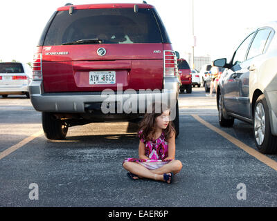 A young girl in a colorful dress sits in a parking lot and waits - Stock Photo