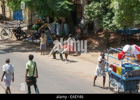 Madurai, India - May 10, 2008. Boys play cricket in the street in Madurai - Stock Photo