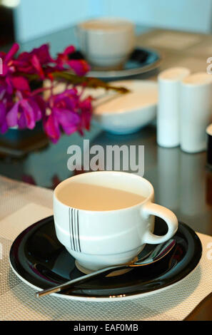 Place Setting:A place setting with a coffee cup, glass, and flatware are set up using a contemporary twist on an - Stock Photo