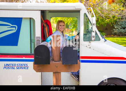 Female United States Postal Service carrier delivering mail in residential neighborhood. Boise, Idaho, USA - Stock Photo