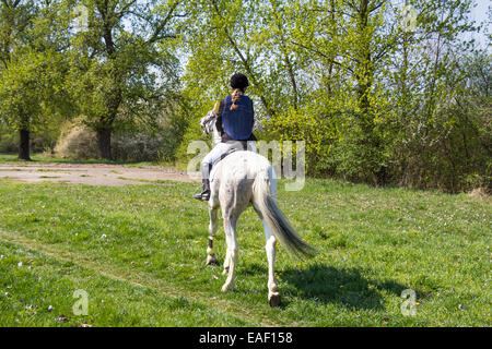 Young girl riding a horse in countryside - Stock Photo