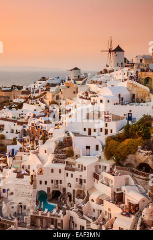 Windmill & white houses at sunset  in the village of Oia, Santorini, Thira, Cyclades Islands, Greek Islands, Greece, - Stock Photo