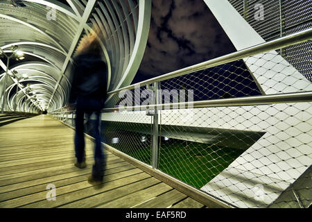Pedestrian passing by the Arganzuela bridge, designed by architect Dominique Perrault. Madrid Rio Park. Madrid. - Stock Photo