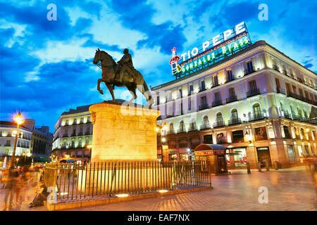 Carlos III statue and TIo Pepe luminous sign at  Puerta de Sol square. Madrid, Spain - Stock Photo