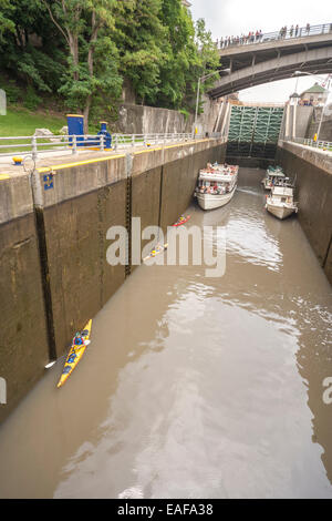 Kayaking Erie Canal Lockport. Three kayaks waiting in lower part of double lift locks 34; 35 with tour cruise boat, - Stock Photo