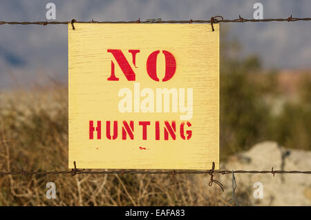 wood no hunting sign wired to a barbed wire fence - Stock Photo