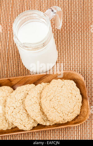 A set of fresh, homemade oatmeal cookies on a wooden tray served with milk. - Stock Photo