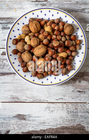 Nuts, peanuts, walnuts assorted in a white dish on white wooden table - Stock Photo