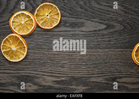 dried orange slices on dark oak table, holiday backdrop - Stock Photo