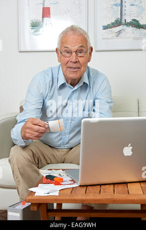 Senior sitting in front of a notebook and papers