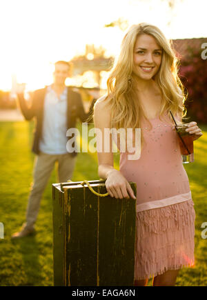 A beautiful lady with a drink glass on her left hand stands against a croquet box with her right elbow rests on - Stock Photo