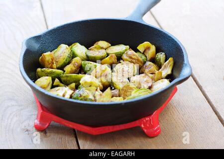 Roasted Brussels sprouts and chestnuts with a balsamic vinegar sauce in a cast iron skillet. - Stock Photo