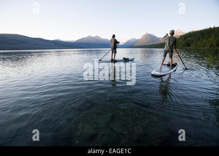 A man and woman stand up paddle boards (SUP) on Lake McDonald in Glacier National Park. - Stock Photo