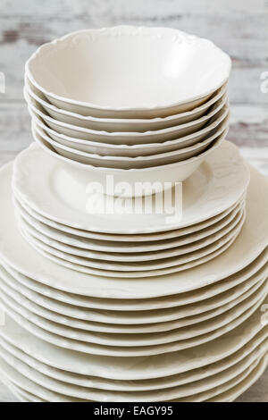 Pile of white porcelain plates lined on white wooden background