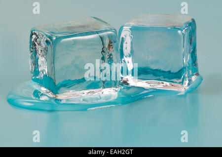 Two ice cubes slowly melting on a shiny surface - Stock Photo