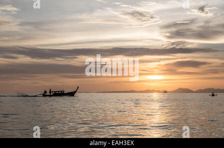 A long tail boat is heading back to the harbour in Ao Nang from Railey beach, Thailand. - Stock Photo