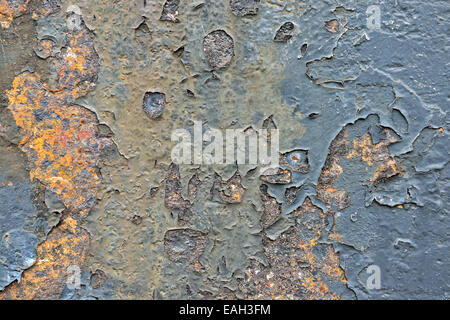 Rusty metal wall as a gloomy background image in red, blue and green tones - Stock Photo