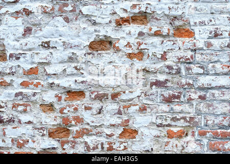old red brick wall with cracked white painting - Stock Photo