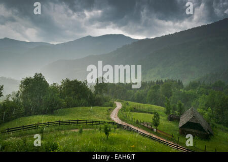 A rainy day in a rural mountain area; a country road and an old house are visible in the near distance. - Stock Photo