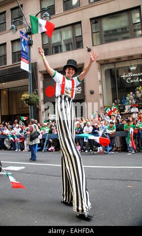 NYC: Stiltwalker waving a Mexican flag at the Mexican Independence Day Parade on Fifth Avenue - Stock Photo
