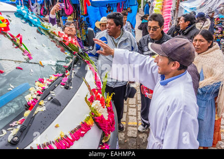 A Catholic priest blesses a van decorated for the annual blessing of the vehicles at the main cathedral in Copacabana, - Stock Photo