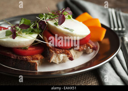 Colorful open faced breakfast sandwich with bacon, tomato, poached egg and sprouts on fresh country bread - Stock Photo