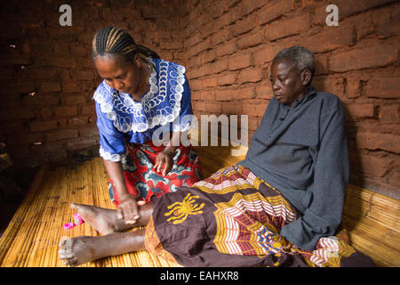 A woman cares for an elderly sick patient at home in Mulanje District, Malawi. - Stock Photo