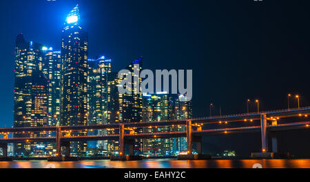 The skyline of Busan lit up at night, with Gwangan Bridge in the foreground. - Stock Photo